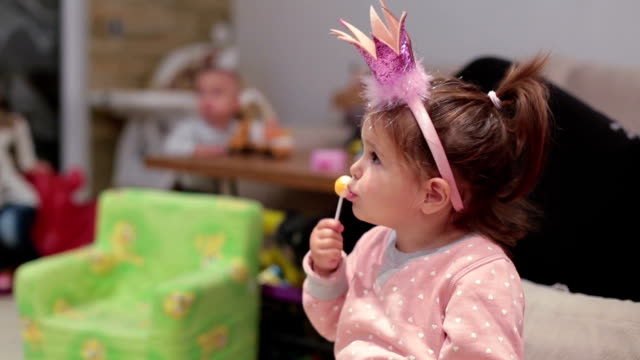 cute baby girl eating licking a lollipop