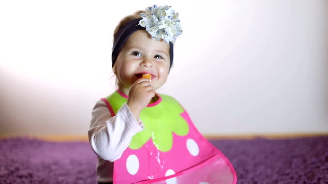 cute baby girl eating orange fruit independently - baby girls stock videos & royalty-free footage