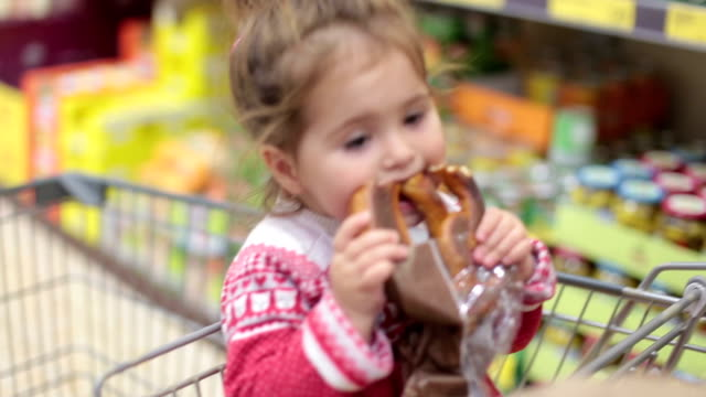 cute baby girl eating pretzel while sitting in shopping cart - austria stock videos & royalty-free footage