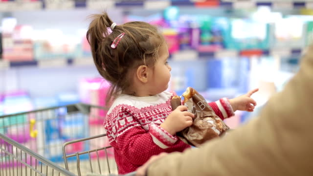 Cute baby girl eating pretzel while sitting in shopping cart