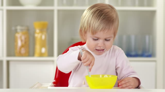 hd: cute baby girl eating with spoon - one baby girl only stock videos & royalty-free footage