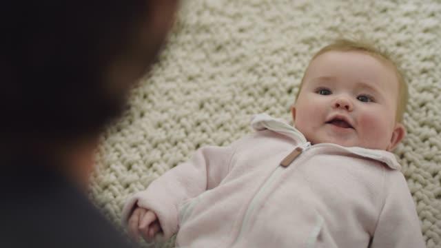 vídeos y material grabado en eventos de stock de cu slo mo. cute baby girl giggles and smiles as she looks up at her father. - padres amos de casa