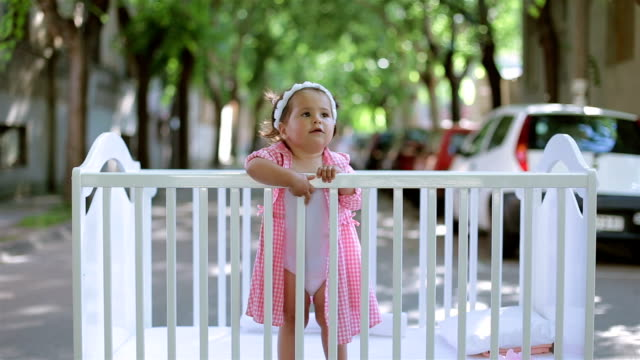cute baby girl in plaid shirt standing in a crib - plaid stock videos and b-roll footage