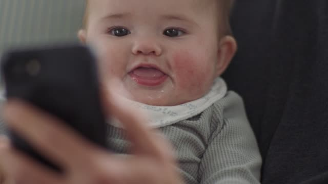 vídeos de stock e filmes b-roll de cu slo mo. cute baby girl looks at smartphone and smiles - família monoparental