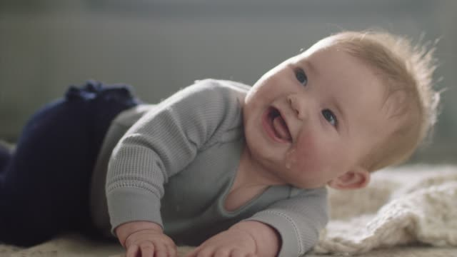 cu slo mo. cute baby girl looks up and smiles as she rolls over on her back on living room carpet. - babies only stock videos & royalty-free footage