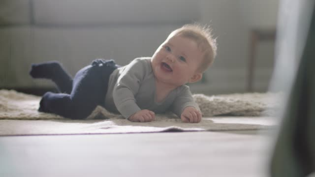 vidéos et rushes de slo mo. cute baby girl looks up and smiles as she rolls over onto her back on living room carpet. - bébé de 0 à 6 mois