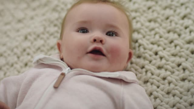 cu slo mo. cute baby girl looks up and smiles at camera as she wriggles around on the floor. - human age stock videos & royalty-free footage