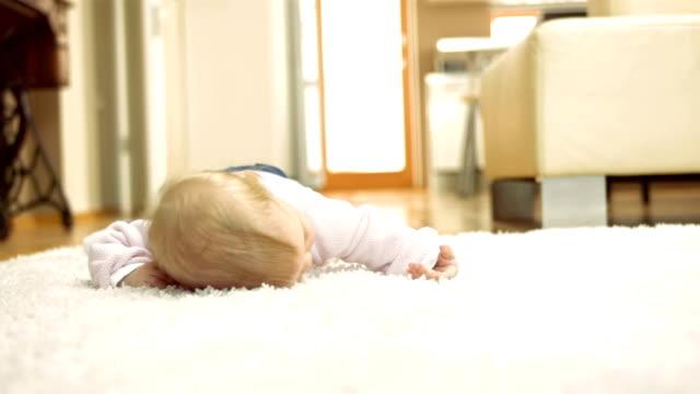 süßes baby mädchen liegen auf dem teppich - krabbeln stock-videos und b-roll-filmmaterial