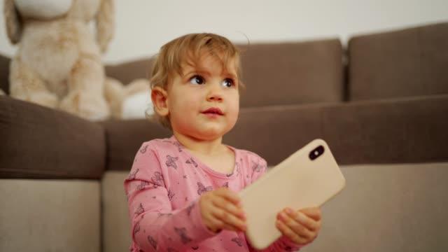cute baby girl playing - abbigliamento da neonato video stock e b–roll
