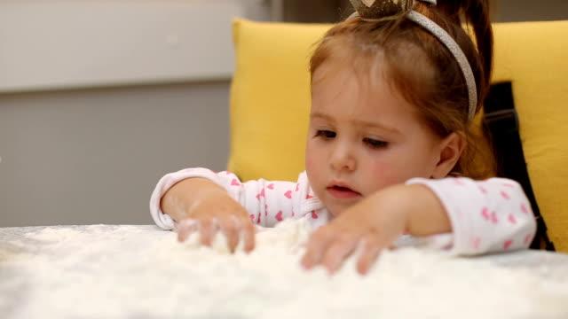 vídeos y material grabado en eventos de stock de linda niña jugando con la harina sobre una mesa y el uso de una corona - cinta de cabeza