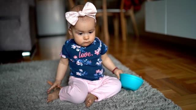 söt bebis flicka leker med plastskål hemma - endast en flickbaby bildbanksvideor och videomaterial från bakom kulisserna