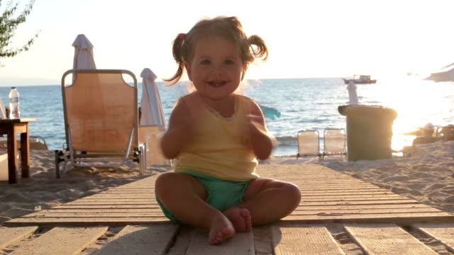 vídeos de stock e filmes b-roll de cute baby girl sitting on a boardwalk and blowing a kiss and clapping - 18 a 23 meses