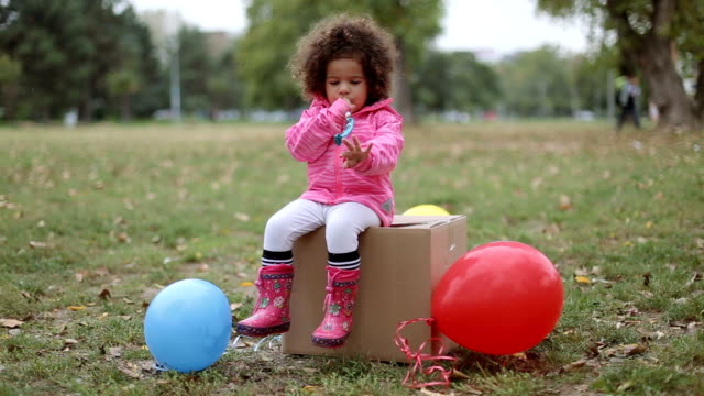 cute baby girl sitting on a cardboard box and blowing party horn