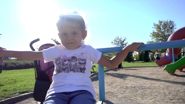 vídeos de stock, filmes e b-roll de spining de menina bonito no carrossel - bebês meninas