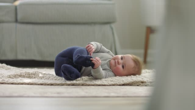 cute baby girl sticks her tongue out and rolls over on her front and back on soft blanket on living room floor. - soft blanket stock videos and b-roll footage