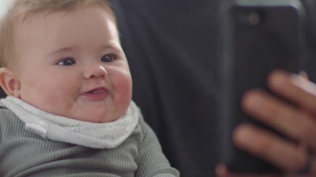 cu slo mo. cute baby girl sticks her tongue out and smiles as she looks at smartphone. - voip stock videos & royalty-free footage