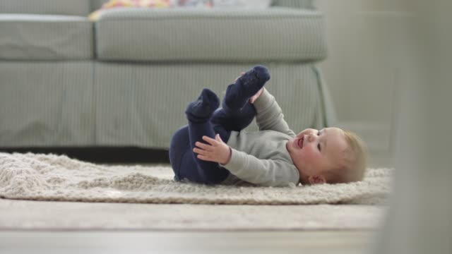 cute baby girl wriggles around and kicks her feet on soft blanket in home living room. - behaglich stock-videos und b-roll-filmmaterial