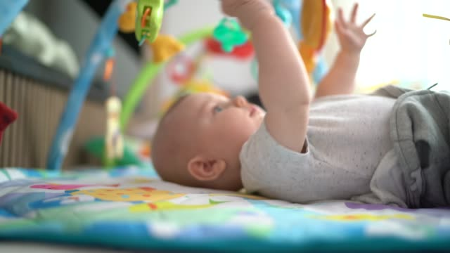 cute baby playing on playmat with hanging mobile - hanging mobile stock videos & royalty-free footage