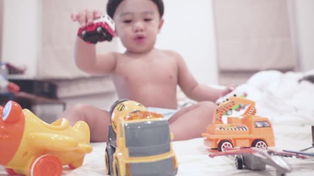 söt baby spelar toy på sängen - endast en pojkbaby bildbanksvideor och videomaterial från bakom kulisserna