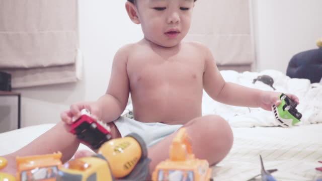 stockvideo's en b-roll-footage met schattige baby speelgoed spelen op het bed - alleen één jongensbaby