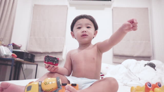 cute baby playing toy on the bed - one baby boy only stock videos & royalty-free footage