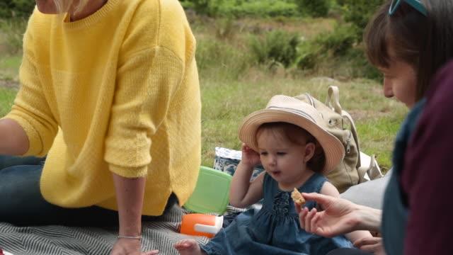 vidéos et rushes de cute baby plays with hat - picnic