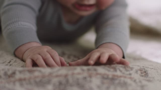 vídeos de stock e filmes b-roll de ecu slo mo. cute baby reaches with her hands and pushes up on living room rug. - aconchegante