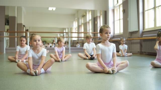 クラスの前に伸びるかわいいバレリーナ - バレエ練習用バー点の映像素材/bロール