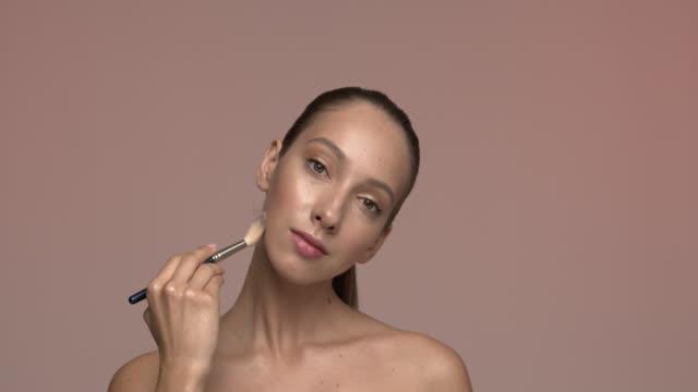 彼女の顔に長い髪と蛍光ペンを持つかわいい美しい女の子は、頬骨に粉末を適用します。 メイクアップ。 - 絵画モデル点の映像素材/bロール