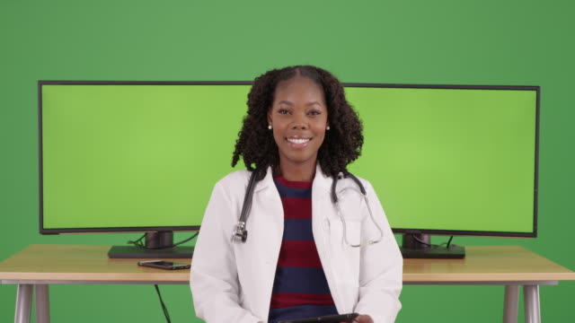 cute black female doctor sitting at office desk, smiling on greenscreen - {{asset.href}} stock videos & royalty-free footage