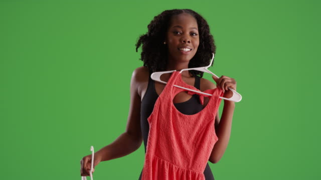 vídeos de stock, filmes e b-roll de cute black female holding dresses against body, smiling at camera on greenscreen - decisions