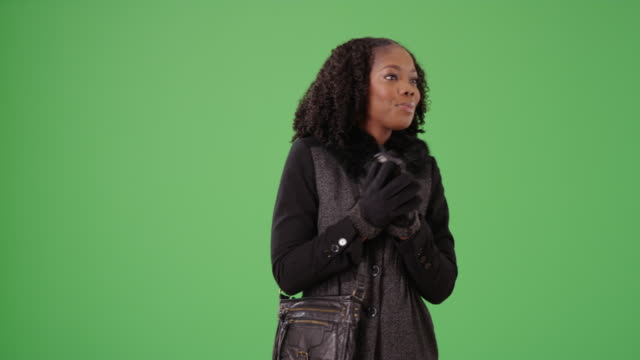 cute black female in winter coat looking around green screen to be keyed - shivering stock videos & royalty-free footage