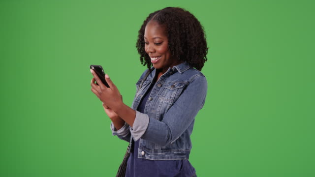 cute black female laughs at funny text message from boyfriend on green screen - denim jacket stock videos & royalty-free footage