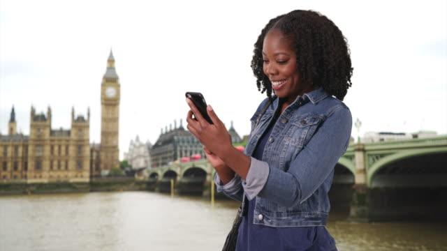 vídeos de stock, filmes e b-roll de cute black female traveling in london laughs at funny text from boyfriend - jaqueta jeans