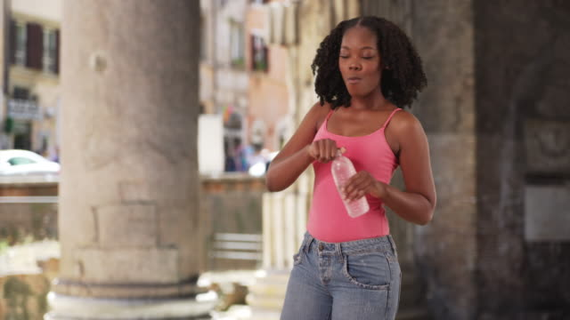 cute black female visiting pantheon in rome takes drink of water, checks phone - pantheon rome stock videos and b-roll footage