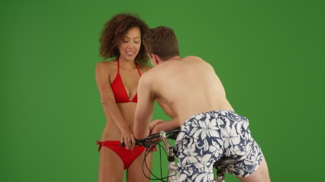 Cute black girl flirting with young male bachelor on bike on green screen