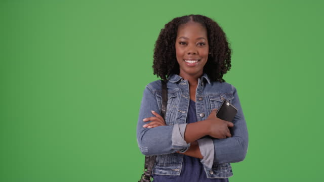cute black woman in denim jacket holding cellphone, smiling on greenscreen - denim jacket stock videos and b-roll footage