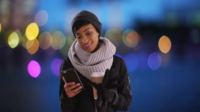 Cute black woman in her 20s texting on phone in setting with blue bokeh lights
