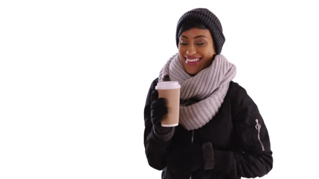 Cute black woman in her 20s wrapped in scarf holding coffee cup in studio