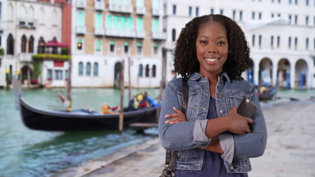 vídeos de stock, filmes e b-roll de cute black woman standing on charming street in venice, smiling at camera - jaqueta jeans