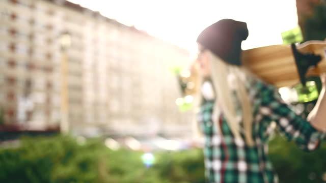vídeos y material grabado en eventos de stock de chica rubia lindo disfrutando en puesta de sol con su longboard - patinaje en tabla larga