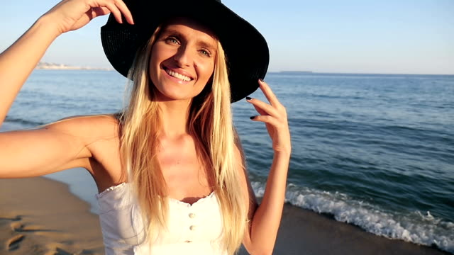 cute blond girl smiling and turning on beach - sun hat stock videos & royalty-free footage