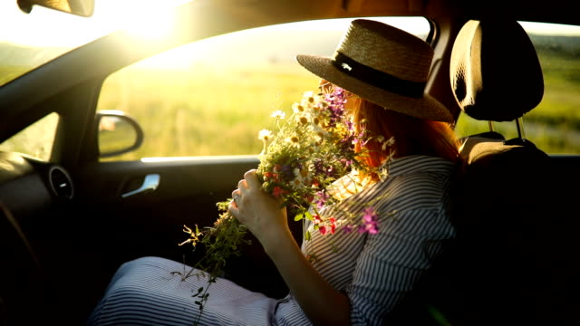 Cute boho style woman with bouquet of spring flowers