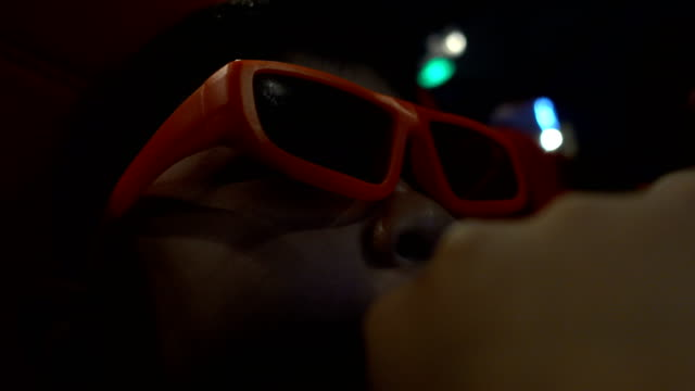 かわいい男の子が映画館で3d 映画を飲んで楽しむ - 3dメガネ点の映像素材/bロール
