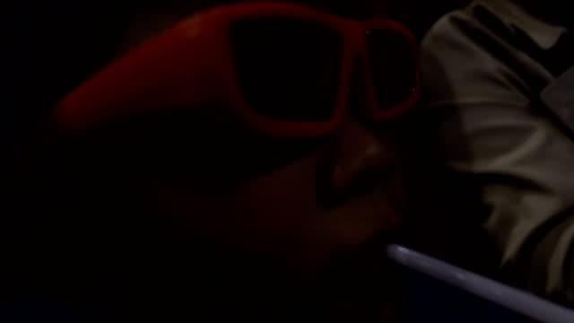 vídeos de stock, filmes e b-roll de menino bonito que bebe e que aprecia a película 3d no cinema - óculos de terceira dimensão