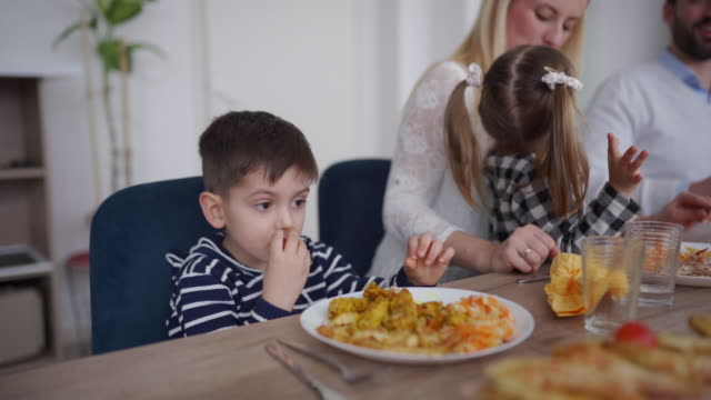 cute boy eating fried potatoes with hands during family lunch at home - 2 3 anni video stock e b–roll