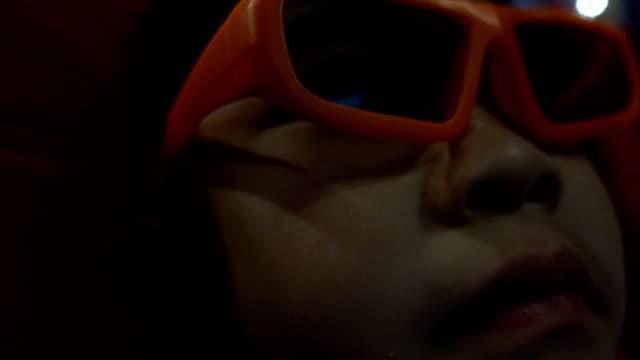 vídeos de stock, filmes e b-roll de menino bonito que come a pipoca e que aprecia a película 3d no cinema - óculos de terceira dimensão