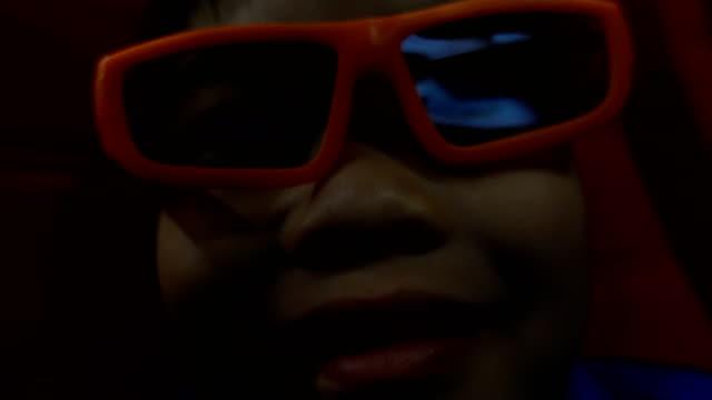 vídeos de stock, filmes e b-roll de menino bonito que aprecia a película 3d no cinema - óculos de terceira dimensão