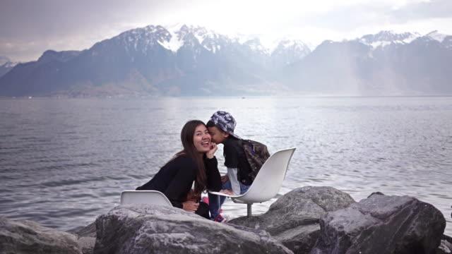 vidéos et rushes de mignon garçon baiser mère au lac léman et les alpes suisses, vevey. - alpes suisses