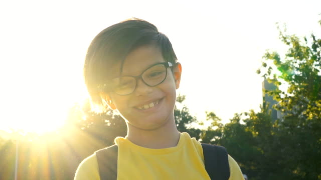 vídeos de stock, filmes e b-roll de menino bonito que olha a câmera no por do sol - óculos